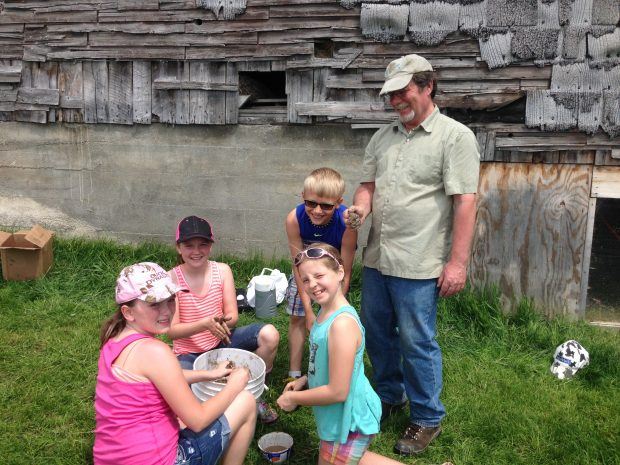 Kids gather around the soil conservationist to learn about soil, and all are smiling.