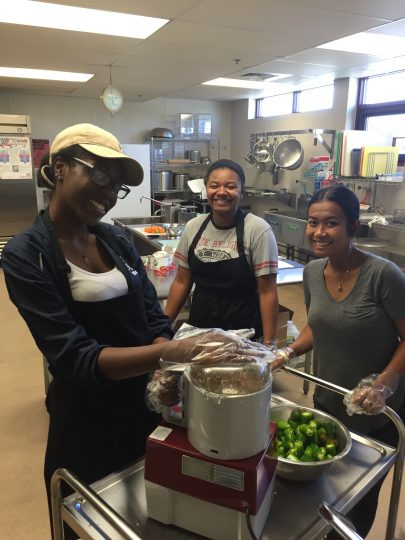 Three young women smile at the camera while operating a food processor in a large commercial kitchen.
