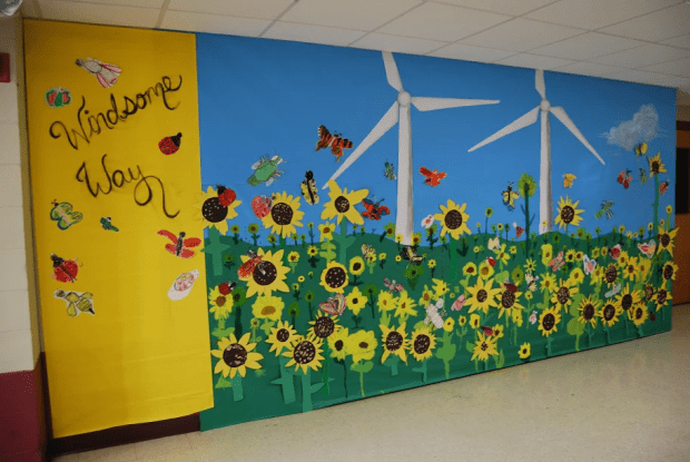 A mural of two wind turbines surrounded by pollinators and sunflowers, with the caption Windsome Way.