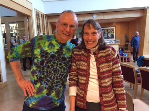 Harry MacCormack wears a tie dyed shirt and smiles with Lynn Coody in what looks like the meeting room of a library.