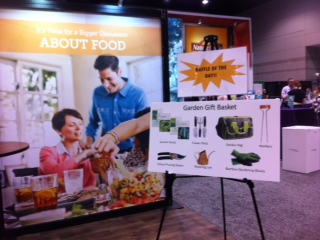 Display of a happy family eating around a table, and the garden gift basket given out by Monsanto at the conference.