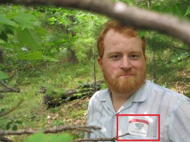 Stanley hiking in the woods still wearing his visitor's pass.