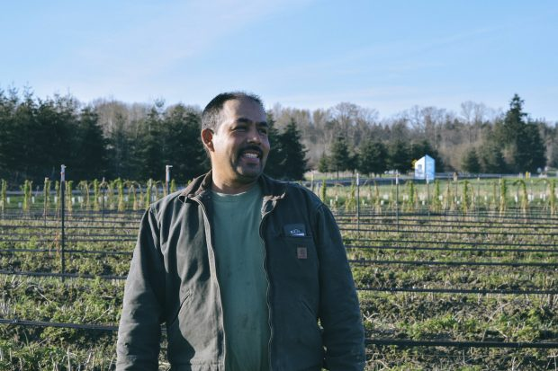 A smiling Washington farmer stands in his field.
