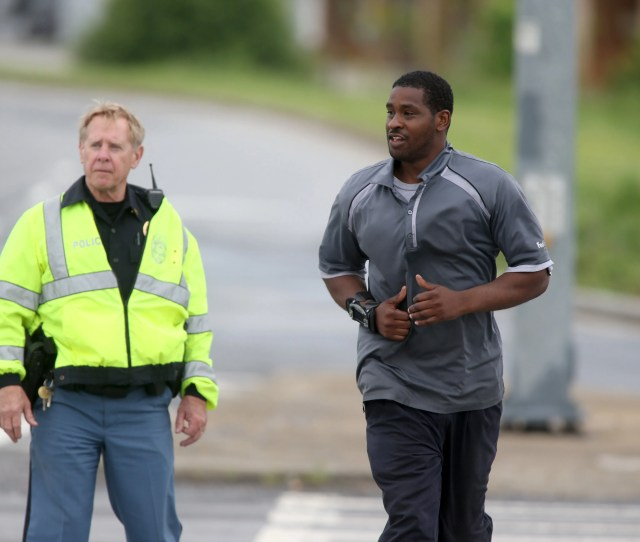 A Cobb County Police Officer Left Escorts A Fedex Employee Leaving The Site Of