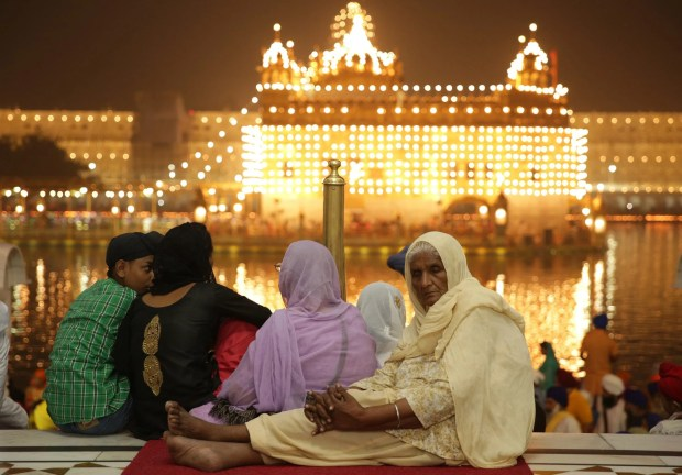 An elderly woman listens to religious hymns while visiting the Golden Temple, the holiest of Sikh shrines, seen in the background, on the occasion of Diwali festival and Bandi Chorh Diwas in Amritsar, India, October 30, 2016.