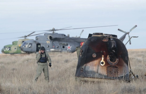 A Russian Soyuz MS-01 space capsule stands on the ground after landing as rescue helicopters land nearby, about 150 km south-east of the Kazakh town of Dzhezkazgan, Kazakhstan, October 30, 2016.