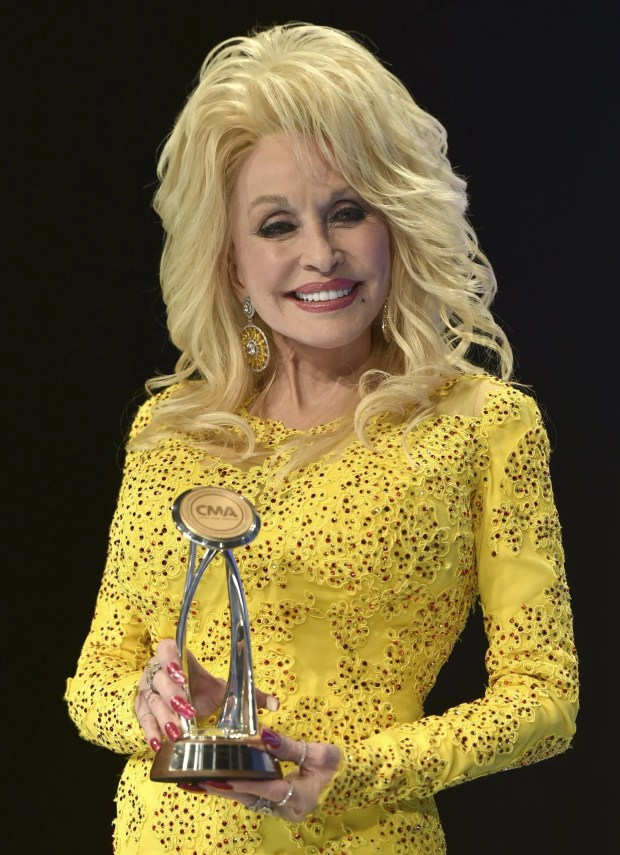 Dolly Parton poses in the press room with the Willie Nelson Lifetime Achievement Award during the 50th annual CMA Awards at the Bridgestone Arena on Wednesday, Nov.