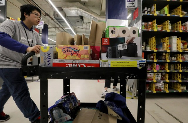 Wilson Yu fills an Amazon Prime order at the warehouse in SoDo. He is one of scores of people who have found work with Amazon through Northwest Center since 2015. (Alan Berner / The Seattle Times)