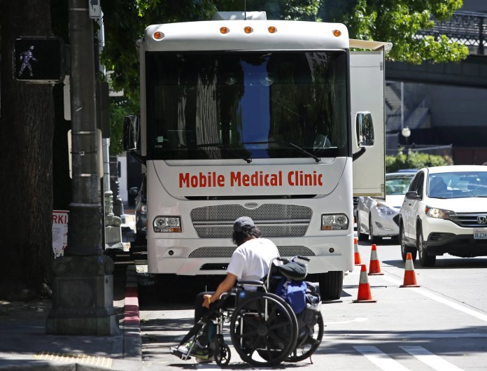 """King County currently has a mobile medical van to treat wounds and prescribe medication-assisted treatment downtown, but the new """"street medicine"""" team will expand on those efforts and take outreach into shelters and encampments. (Ken Lambert / The Seattle Times)"""