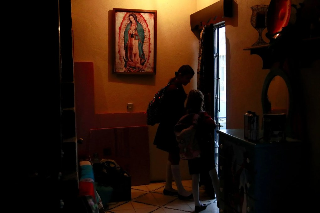 Below an image of Our Lady of Guadalupe, Maya and Catalina leave their house for school. (Erika Schultz / The Seattle Times)