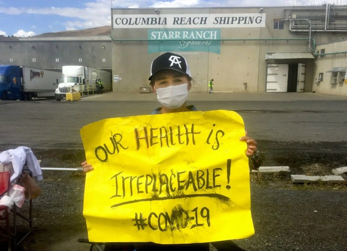 Rosalinda Gonzalez walked off her quality-control job at the Columbia Reach fruit  warehouse in Yakima on May 14, and spent this week on a picket line. Striking workers across the area want more-stringent safety measures to reduce the risk of coronavirus infection, as well as hazard pay. So far, 29 workers at Columbia Reach have tested positive for the coronavirus, according to the Yakima County Health District.  (Hal Bernton / The Seattle Times)
