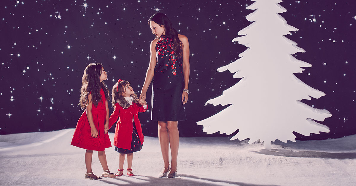 mother and daughters in holiday christmas clothing at night with stars tree