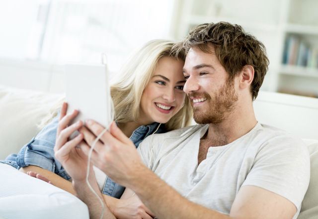 Happy young couple at home video chatting using app on a tablet computer