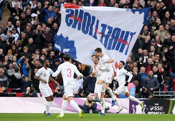 Kane is mobbed after netting a late winner for England, securing their Nations League semi-final spot