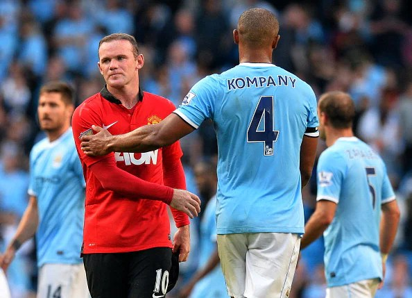 Manchester City's  Vincent Kompany (R) shakes hands with Manchester United's Wayne Rooney (L) after their teams clashed in the local derby at the Etihad Stadium in Manchester, England, on September 22, 2013. (Getty Images)