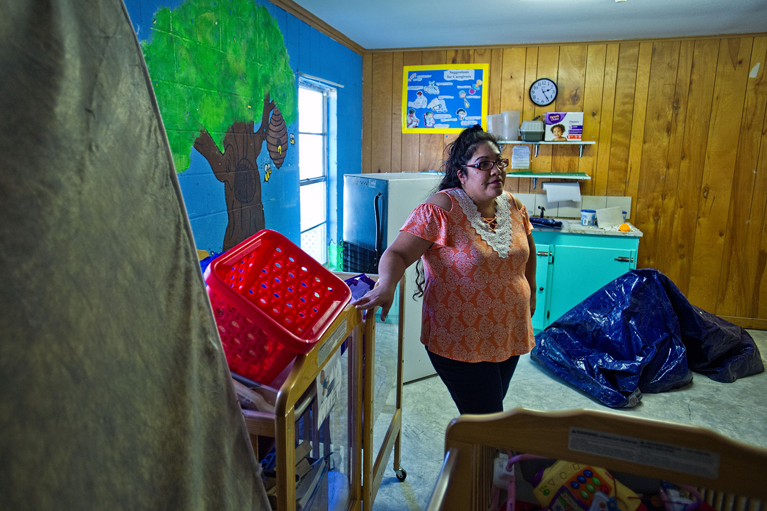 LaVeta Rodriguez, director of the Little Lights Learning Center, stands among the unused cribs, toys and equipment in the baby room at the center.