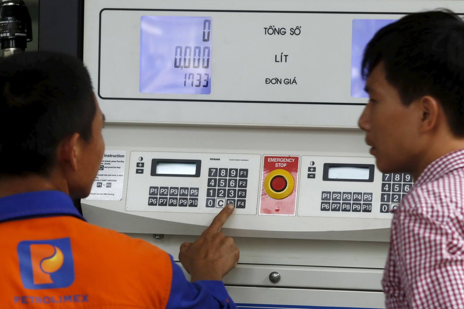 An employee keys in the price of petrol at a pump at a petrol station in Hanoi, Vietnam September 3, 2015. Photo: Reuters/Kham