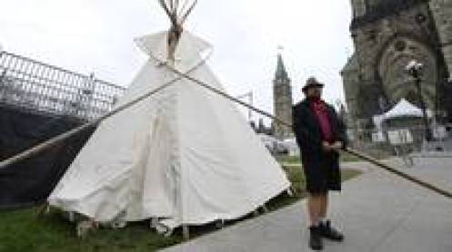A man stands outside a large teepee erected by Indigenous demonstrators to kick off a four-day Canada Day protest in front of Parliament Hill in Ottawa on Thursday. (Justin Tang/The Canadian Press)