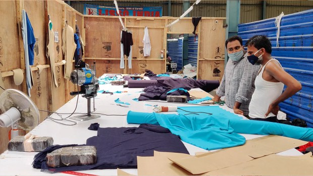 Mrityunjay Sharma, 29, who owns a clothing unit, with a designer who works with him | Sajid Ali | ThePrint