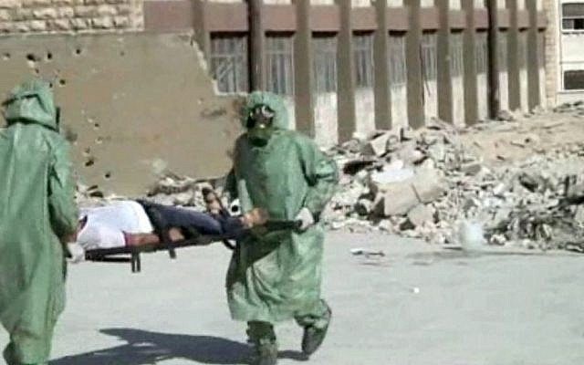 Illustrative photo: this image, from a video posted on September 18, 2013, shows Syrians in protective suits and gas masks conducting a drill on how to treat casualties of a chemical weapons attack, in Aleppo, Syria (AP)