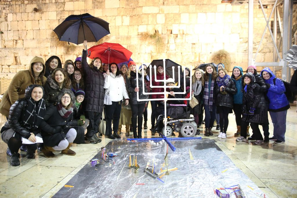 women hold hanukkah candle lighting