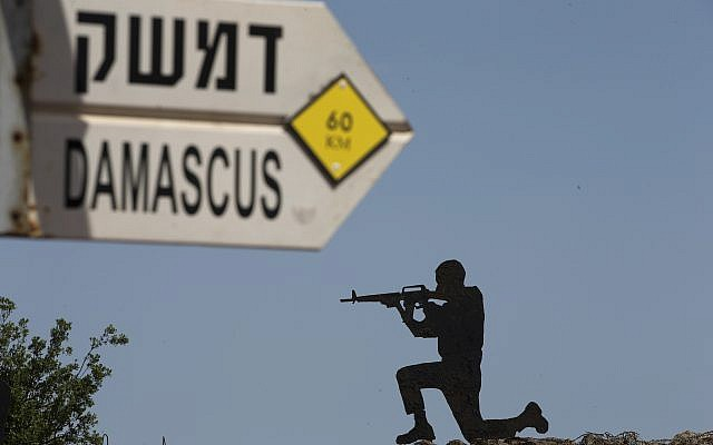 A mock road sign for Damascus, the capital of Syria, and a cutout of a soldier, are displayed at an old outpost in the Golan Heights near the border with Syria, May 10, 2018. (AP Photo/Ariel Schalit)