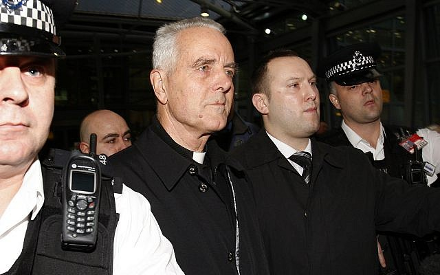 Bishop Richard Williamson, second from left in foreground, is escorted out of Heathrow airport by police and security officers after arriving on a flight from Argentina, in London, Feb. 25, 2009 (AP Photo/Kirsty Wigglesworth)