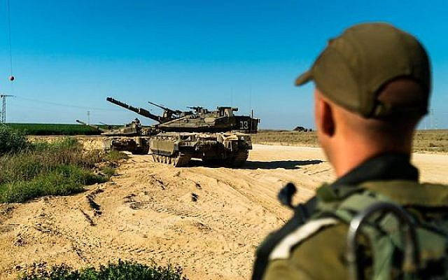An IDF soldier and a tank during a military drill near the Gaza Strip, late July 2019. (IDF)