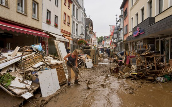 Residents and shopkeepers try to clear mud from their homes and move unusable furniture outside in Ahrweiler, western Germany, on July 17, 2021. (Thomas Frey/dpa via AP)