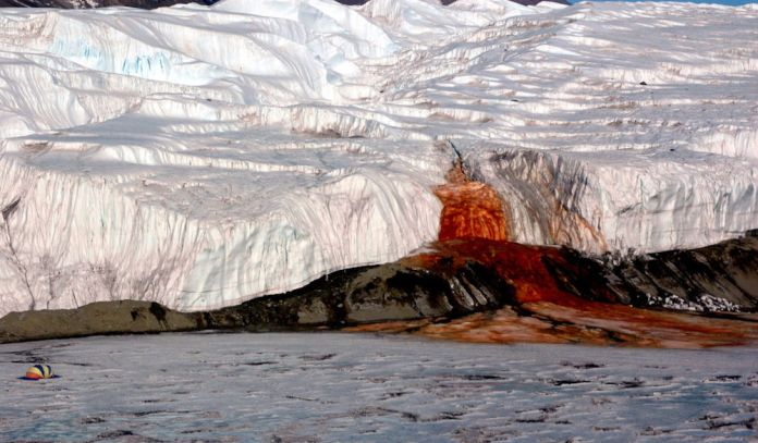 The Blood Falls seeps from the end of the Taylor Glacier into Lake Bonney. The tent at left provides a sense of scale for just how big the phenomenon is. Scientists believe a buried saltwater reservoir is partly responsible for the discoloration, which is a form of reduced iron.
