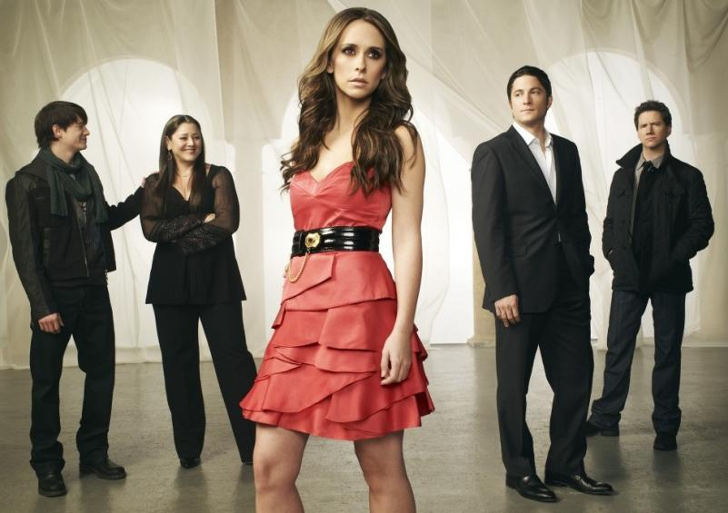 Ghost Whisperer cast in black in the background, with Melinda at the front and centre in an orange-y dress, looking away from the camera.