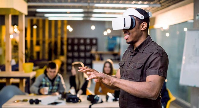 A man wearing a virtual reality headset stands before colleagues in an office space