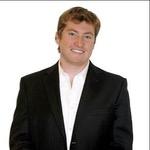 Passport picture of Colin Klinkert in dark suit and white short, no tie, smiling
