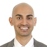 Passport snap of Neil Patel wearing a suit and smiling broadly