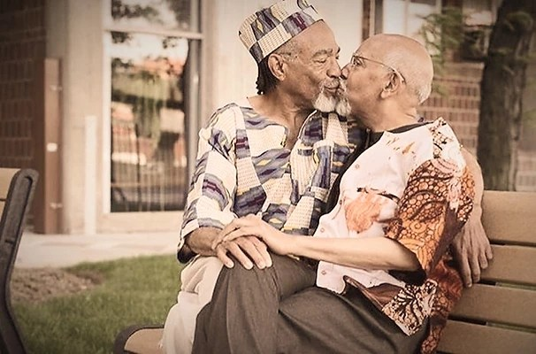 Photo of two male people of colour, sat together on a bench, sharing a kiss.