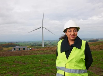 Image of Sadia Maqsood in a field, in front of a wind turbine.