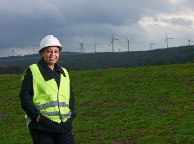 Image of Sadia Maqsood in front of a field, with wind turbines in the background.