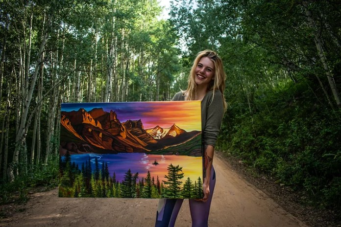 An artist holds her painting of St. Mary Lake in Glacier National Park, MT