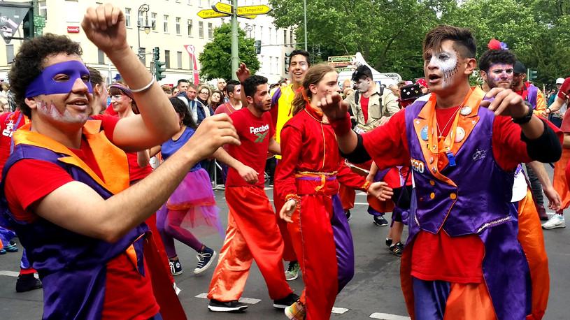 Na obrazku są mężczyźni tańczący podczas Karnawału Kultur.