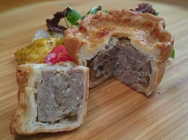 A pork pie with a slice cut out