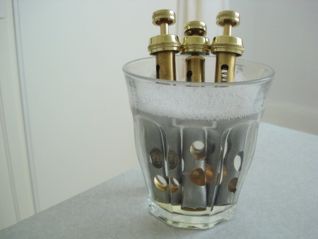 Trumpet valves soaking in a glass of soapy water