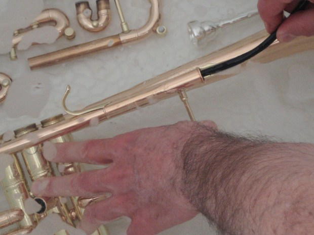 Cleaning a trumpet with a snake brush