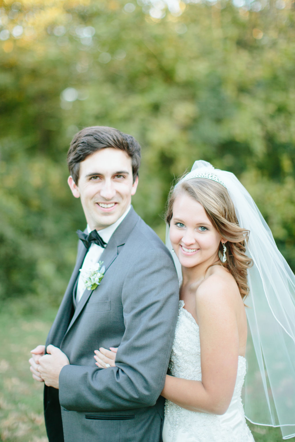 Bride in gown and groom in gray suit on wedding day portraits