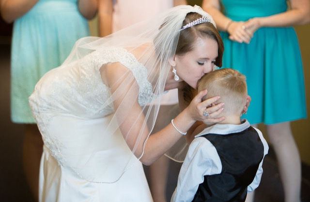 Bride kissing ring bearer on wedding day