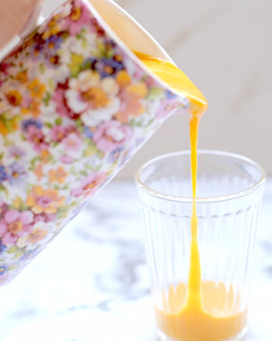 Mango lassi being poured out of floral jug with a marble background.