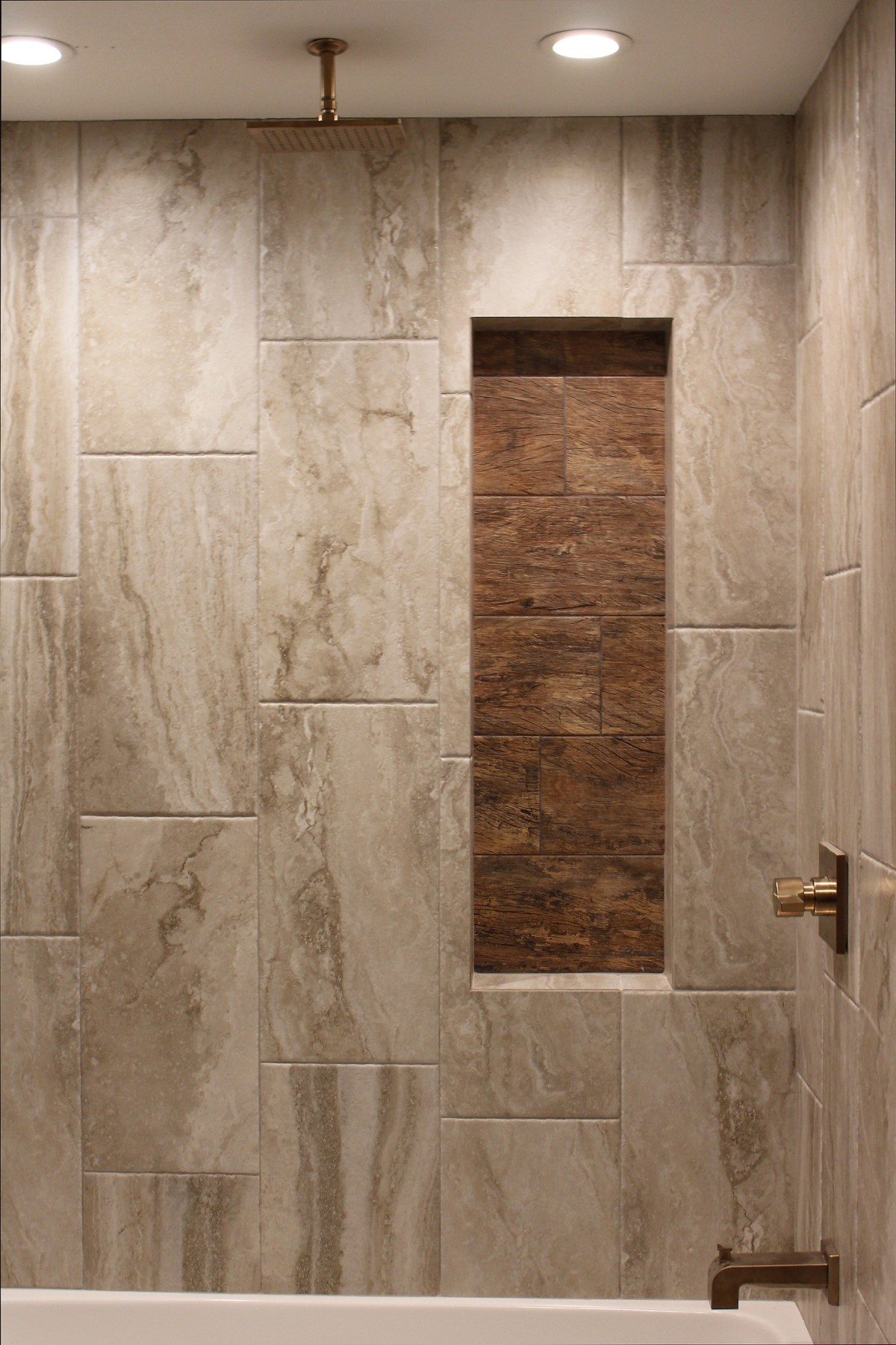 Bathroom remodel uses wood look tile in shower niche