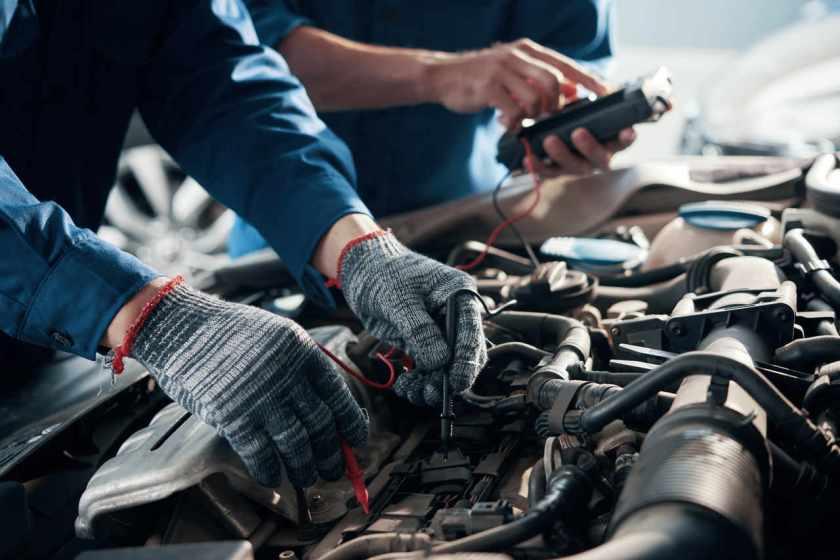 mecanico faz reparo no motor do carro com capo aberto