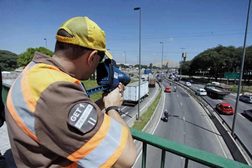 agente de transito fiscaliza velocidade de carros na rodovia com radar eletronico em sao paulo