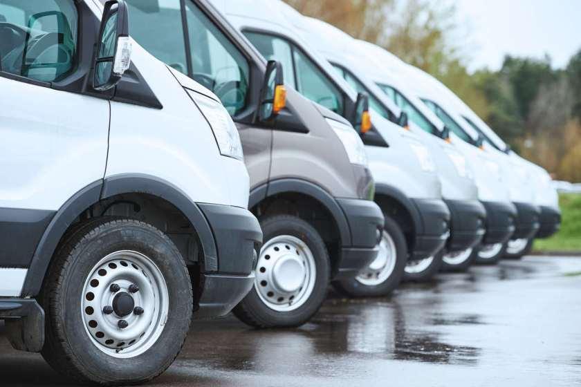 vans corporativas paradas ao lado umas das outras em estacionamento de frotas da empresa