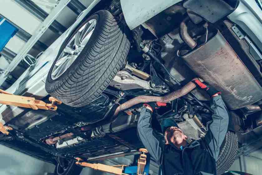 mecânico faz revisão no escapamento de carro em oficina mecanica